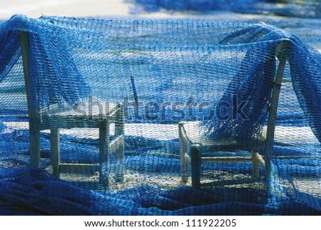 Fishing-net hanging on two chairs, Spain - stock photo