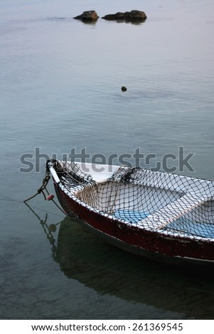 Fishing net on a small rustic boat in the sea. - stock photo
