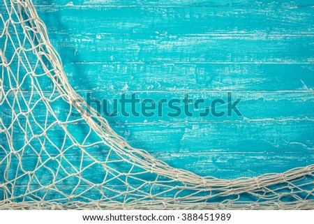 Fishing net on old blue board background with copy space - stock photo