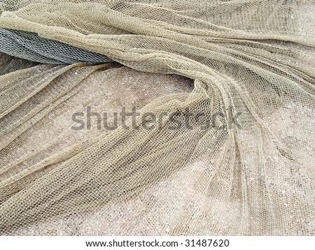 Fishing net on sand. - stock photo