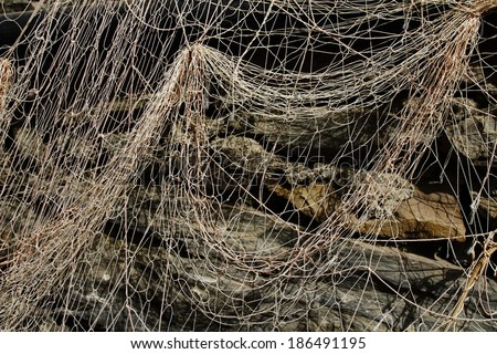 Fishing net on the old stone wall - stock photo