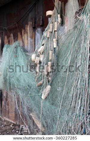 fishing net with floats drying on the wall