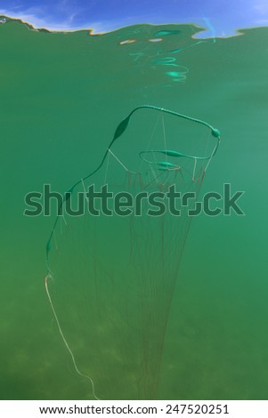 Fishing net with lifting bodys underwater in the freshwater lake near the surface - stock photo