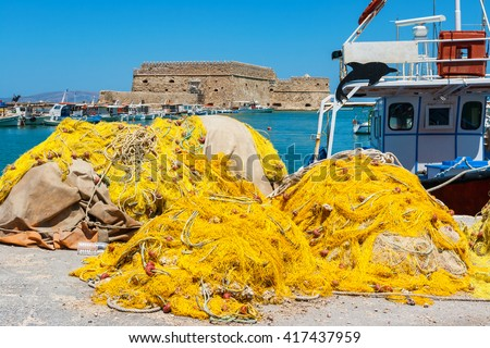 Fishing nets and fishing boats near Venetian fortress in the port of Heraklion. Crete, Greece - stock photo