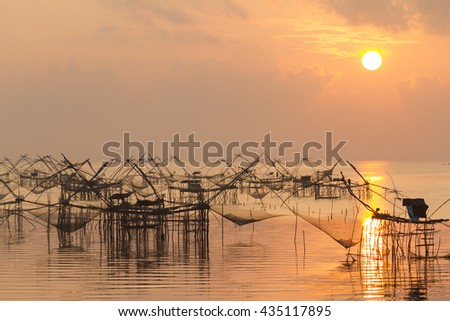 Fishing nets in the lake in Southern part of Thailand in gold warm morning light - stock photo