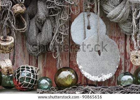 Fishing nets, round stone sinkers, cork and glass floats at boathouse wall in Norway - stock photo