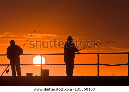 Fishing off the pier, sunset - stock photo