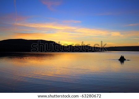 fishing on morning lake with mountain sunrise - stock photo