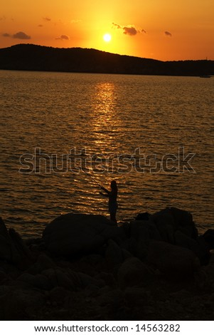 Fishing on soft sunset on Sardinia, Capo Malfatano, Italy, september, mediterranean sea