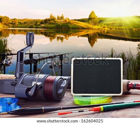 fishing on the lake at sunset - stock photo