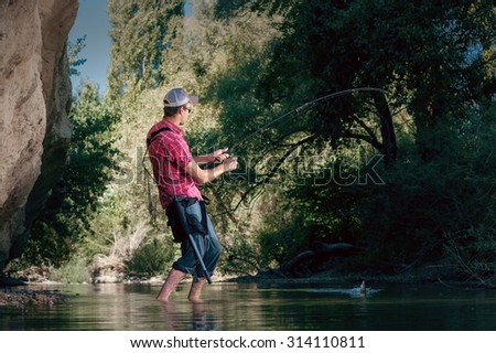 Fishing on the river. Man catches a fish on a lure Spinning. Fisherman with a fishing rod. - stock photo