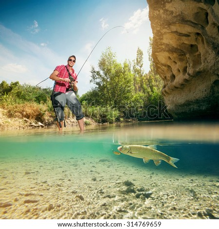 Fishing on the river. Young fisherman catches a fish. Fish closeup underwater. - stock photo