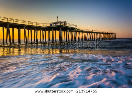 Fishing pier and waves on the Atlantic Ocean at sunrise in Ventnor City, New Jersey. - stock photo