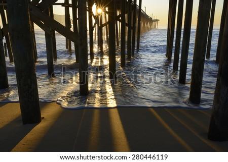 Fishing Pier Pillars and Sunburst at Sunrise - stock photo