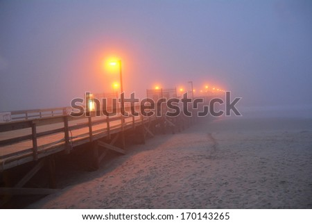Fishing pier reaching out to ocean on a foggy night at dusk - stock photo