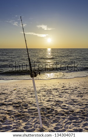 Fishing pole against ocean at sunset - stock photo