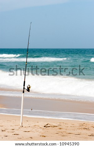 Fishing pole on beach - stock photo