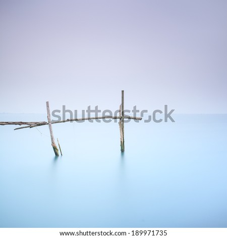 Fishing poles for clams and mussels and soft water on a quiet foggy landscape. Long exposure photography - stock photo