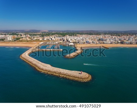 Fishing port and beaches of Quarteira, the view from the sky. Aerial. Fish industry in Portugal