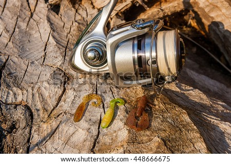 Fishing reel on the natural background. Assorted of various kind of fishing baits. Spinning on the old tree with brown bark. - stock photo