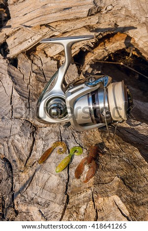 Fishing reel on the natural background. Assorted of various kind of fishing silicon baits on the old tree with brown bark. - stock photo