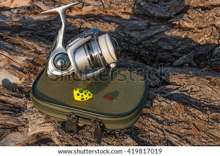 Fishing reel on the natural background. Fishing bait with small red silicone worm. Objects on the green box for fishing bait on the old tree with brown bark. - stock photo