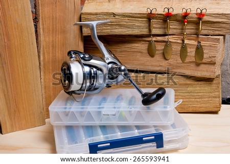 Fishing reel with metal baits on wooden background. Different tips of the fishing jig baits. - stock photo