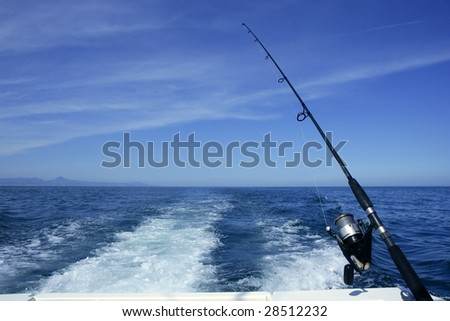 Fishing rod and reel on a boat, vacation on blue sea and summer sky