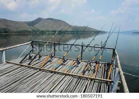 Fishing rod and reel on a lake  - stock photo