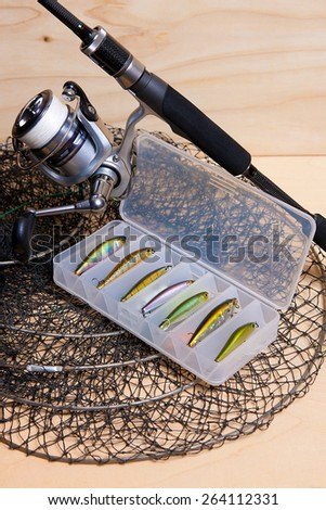 Fishing rod and reel with box for baits and fishpond. - stock photo