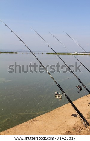 Fishing-rod at the lake under blue sky