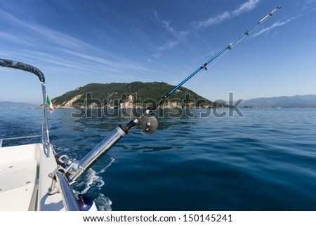 fishing rod from the boat in front of island - stock photo