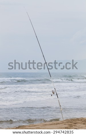 Fishing rod in the sand Coastline blurred in background