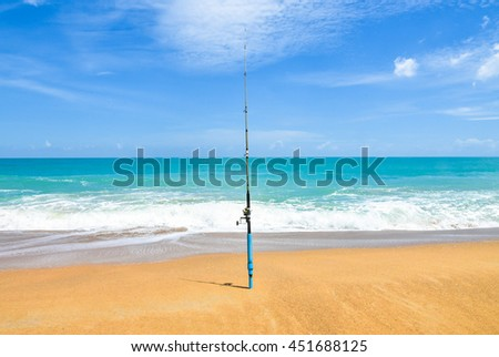 Fishing rod on empty beach with beautiful ocean. rod spinning with spoon-bait at the beach fishing rod on a beach against a horizon and nice sea - stock photo