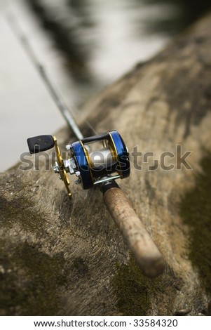 Fishing rod on log in river - stock photo