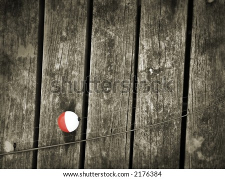 Fishing rod on old boards - stock photo