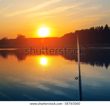 Fishing rod sunset and bobber on water - stock photo