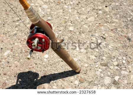 Fishing rod with red reel.