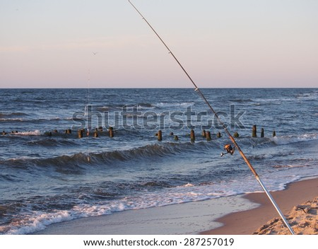 fishing-rod with spinning-wheel on sea background - stock photo