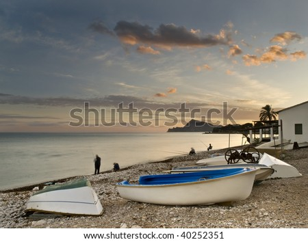 Fishing scene with some boats in the foreground, taken at sunset in Altea, a beautiful town located in the Costa Blanca of Spain. - stock photo