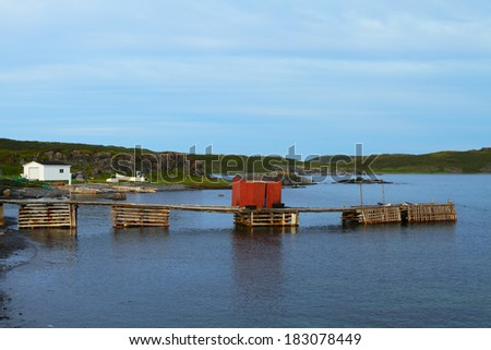 Fishing shack and boats in Nordic landscape - stock photo