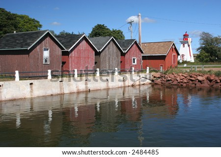 Fishing shacks  and lighthouse at the wharf in Victoria-by-the-Sea , Prince Edward Island. - stock photo