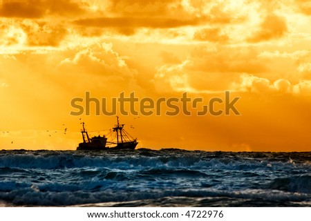 fishing ship at sea with sunset - stock photo