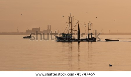 Fishing ship sailing home in sunset - stock photo