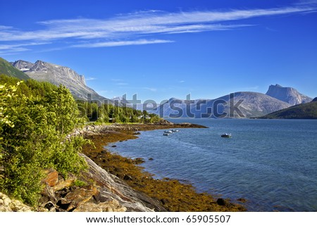 Fishing small house on the bank of mountain lake - stock photo