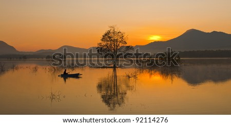 Fishing spinning at sunset. Silhouette of a fisherman. - stock photo
