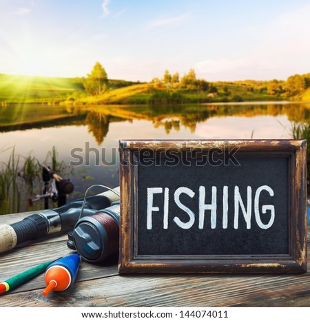 fishing tackle and a blackboard on a background of lake at sunset - stock photo