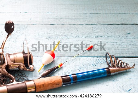Fishing tackle on wooden blue background - stock photo