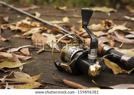 Fishing tackle on wooden weathered surface. - stock photo