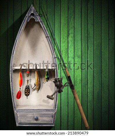 Fishing Tackle - Small Boat / Green wooden background with small boat and fishing tackle - stock photo